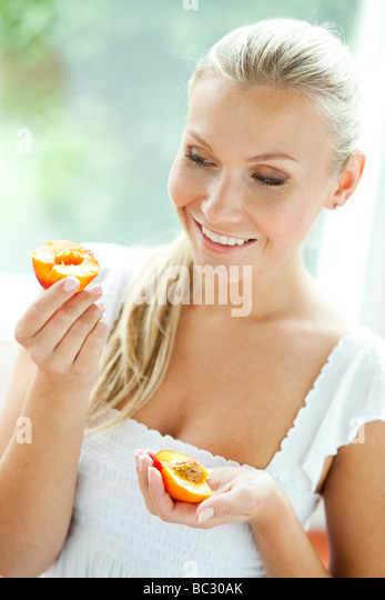 Woman eating Nectarine - Stock Image