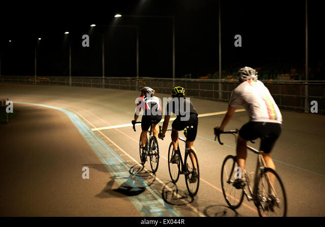 Cyclists cycling on track at velodrome, rear view - Stock Image