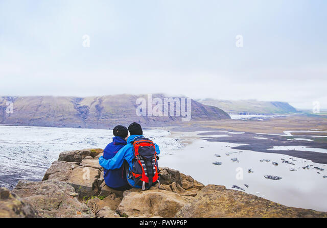couple of hikers travel in Iceland, two backpackers enjoying view of glacier and mountain landscape - Stock Image