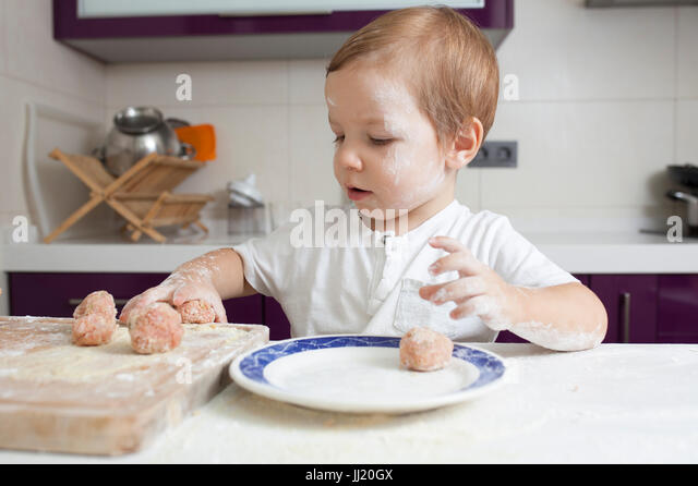 Baby boy preparing meatballs. He is playing with just kneaded meatballs - Stock Image