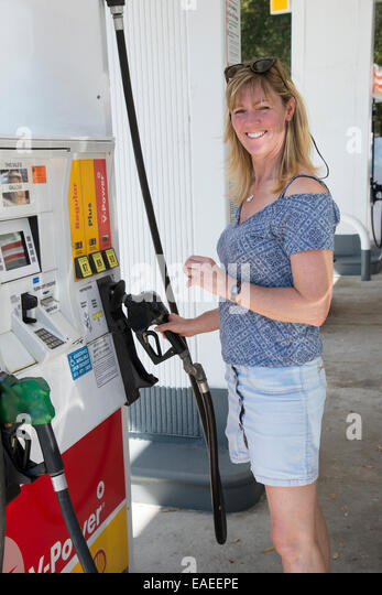 Woman motorist at a gas station in USA selecting grade of petrol - Stock Image