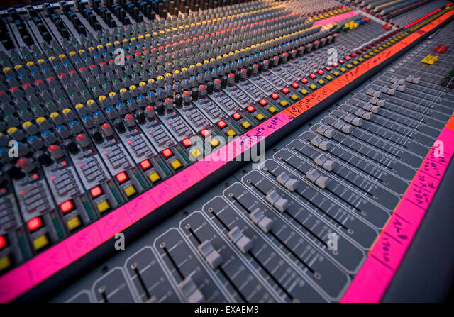 Vertical shot of a mixing deck/ soundboard with equalizer, levels controls and lit leds. - Stock-Bilder