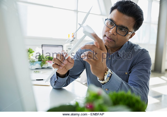 Serious scientist examining wind turbine model in laboratory - Stock Image