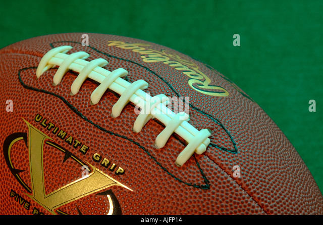 an american football on a green background - Stock Image