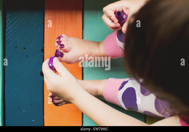 Elevated view of a girl messily painting her toes - Stock Image