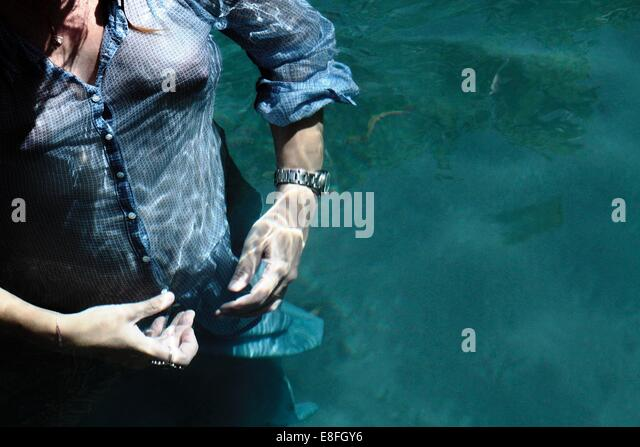 Woman swimming fully clothed underwater - Stock Image