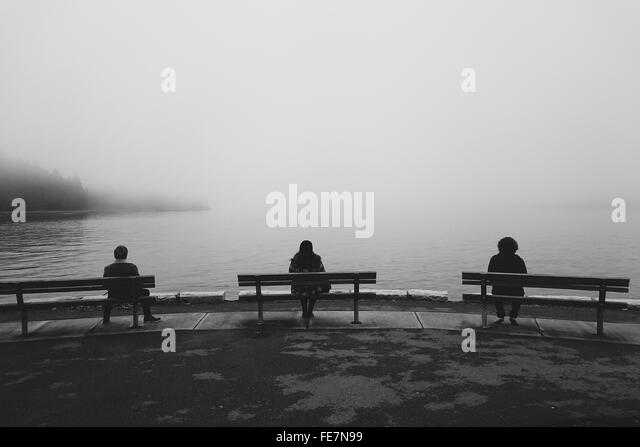 Three People Sitting On Benches At Lakeshore - Stock Image