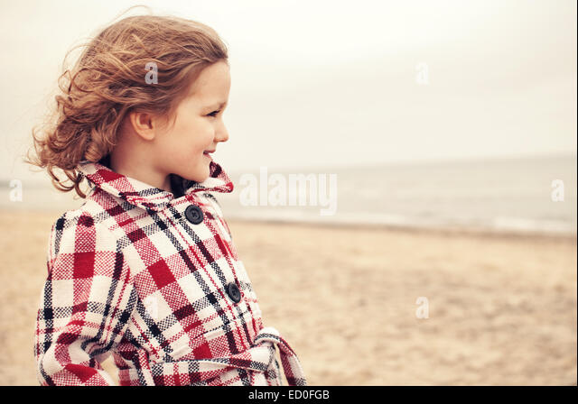 Small girl (2-3) in coat on beach - Stock Image
