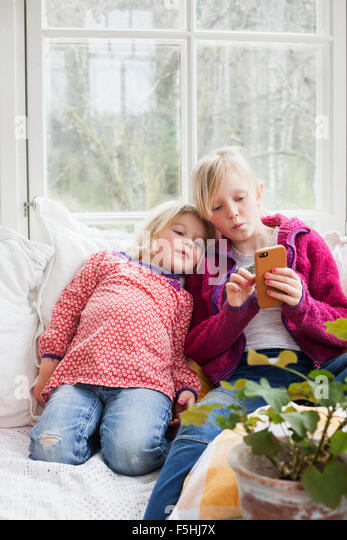 Sweden, Sisters (4-5, 10-11) using smart phone at home - Stock-Bilder