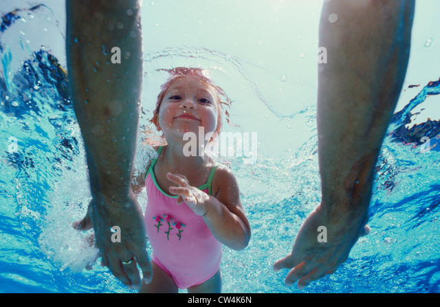 Close-up of father's hands reaching out to his daughter underwater - Stock-Bilder