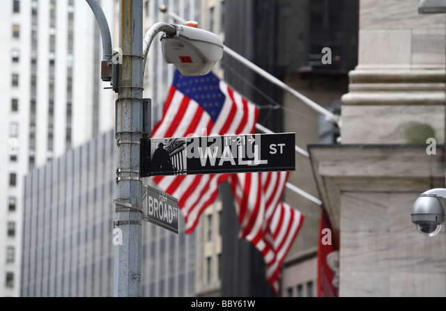 Wall Street sign and American flagon Stock Exchange facade - Stock Image