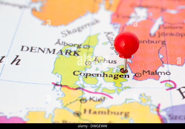 Round red thumb tack pinched through Copenhagen on Denmark map. Part of collection covering all major capitals of - Stock Image