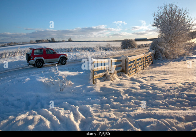 4x4 vehicle in winter snow on a country road in North Yorkshire in the United Kingdom - Stock Image