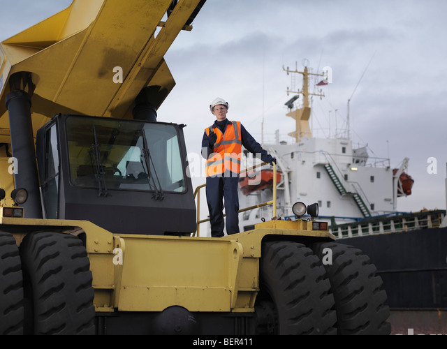 Port Worker Standing On Container Grab - Stock Image