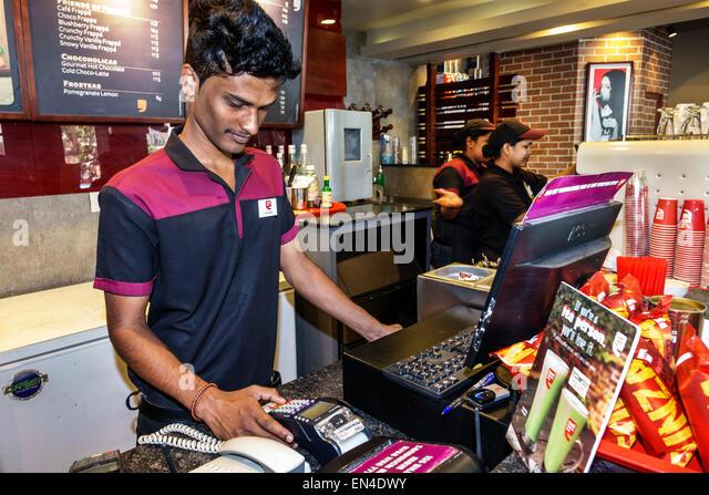 Mumbai India Asian Churchgate Jamshedji Tata Road Cafe Coffee Day restaurant inside counter man employee cashier - Stock Image