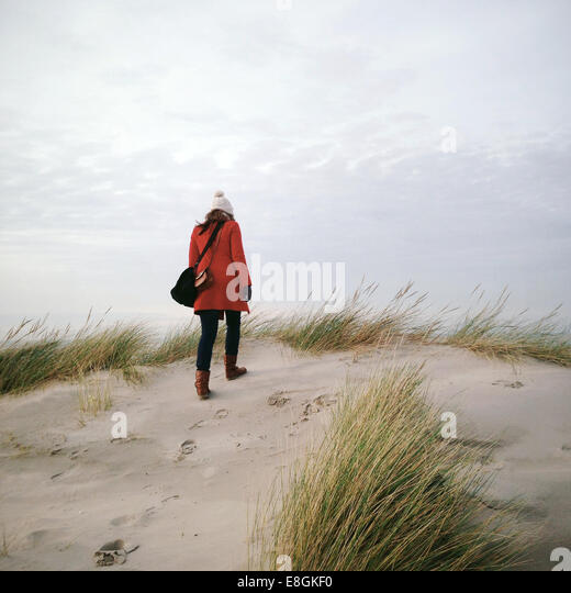 Rear view of woman walking on beach in winter - Stock Image