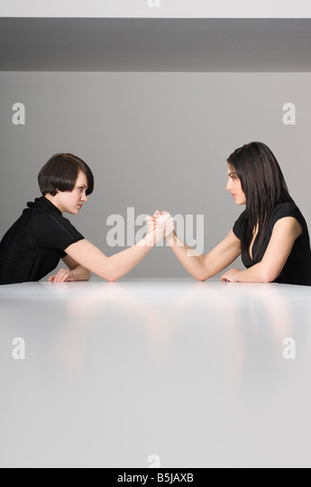 two young businesswomen doing arm wrestling at conference table - Stock Image
