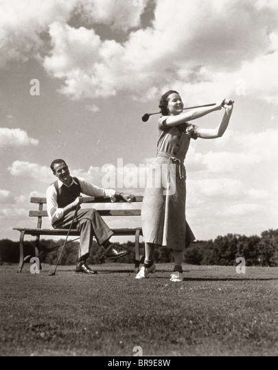 1930s COUPLE PLAYING GOLF MAN ON BENCH WOMAN SWINGING CLUB - Stock Image