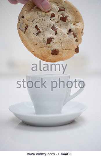Hand dipping large chocolate chip cookie in small coffee cup - Stock Image