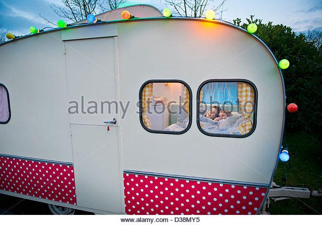 Children relaxing in bed in camper - Stock-Bilder