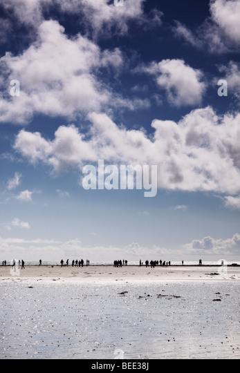 people walking along a causeway - Stock Image