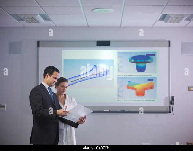 Scientists discuss notes next to designs - Stock Image