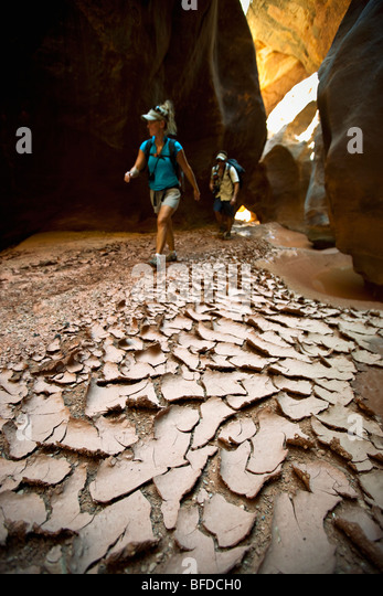 A man and woman hiking through a narrow canyon past dried and cracked mud in Utah. - Stock-Bilder