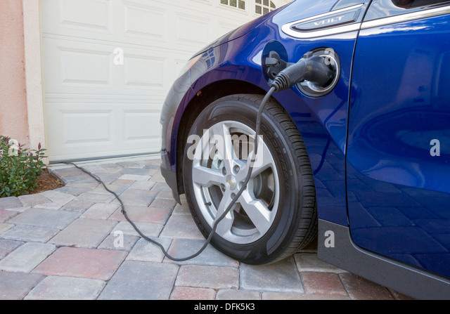 Chevrolet Volt plug-in electric car with connector plugged in charging, at home in a driveway - Stock Image