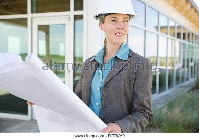 Sustainable energy engineer visualizing blueprints - Stock Image