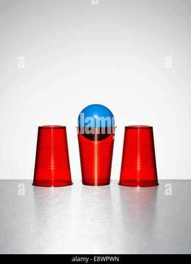 Blue ball in middle of three red cups - Stock Image