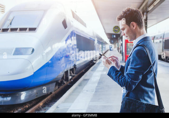 man using mobile application on his smartphone at train station, business travel - Stock Image