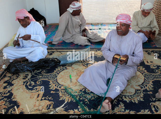 United Arab Emirates, Dubai, old men mending fishing nets, - Stock Image