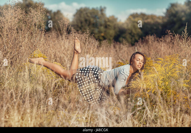Girl flies over the meadow with yellow wildflowers. - Stock Image