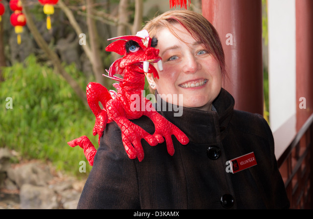 Happy young volunteer host with dragon on her shoulder, Dr Sun Yat Sen Park and Gardens - Stock Image