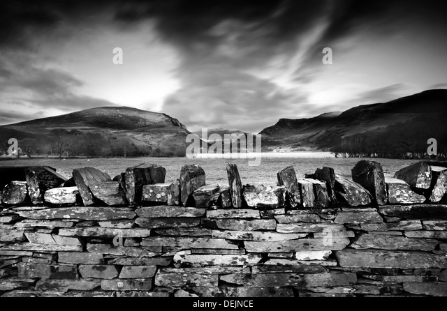 Stone wall and sunset in North Wales, UK, summit of Snowdonia in background - Stock-Bilder
