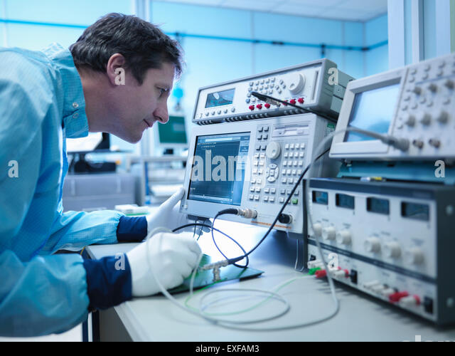 Worker checking electronics in clean room laboratory - Stock Image