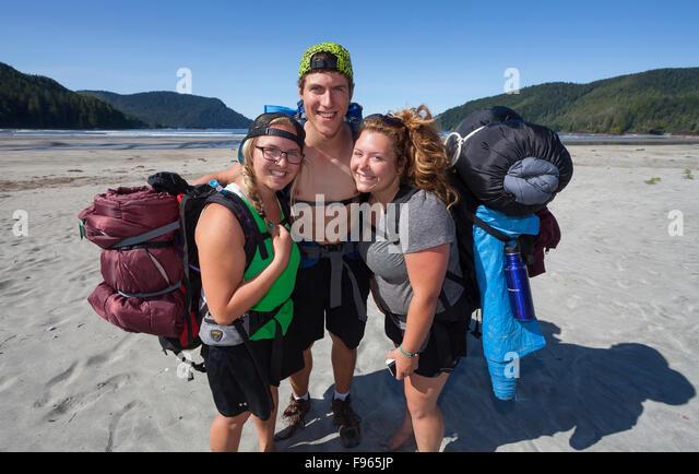 Three friends hiking, hug after arriving at San Josef Bay. - Stock Image