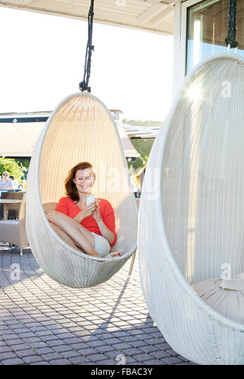 Finland, Uusimaa, Helsinki, Kaivopuisto, Smiling young woman using smart phone in swing chair - Stock Image