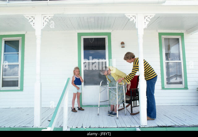 3 generations of women daughter helping elderly mother to sit in her rocker on her front porch while young daughter - Stock Image