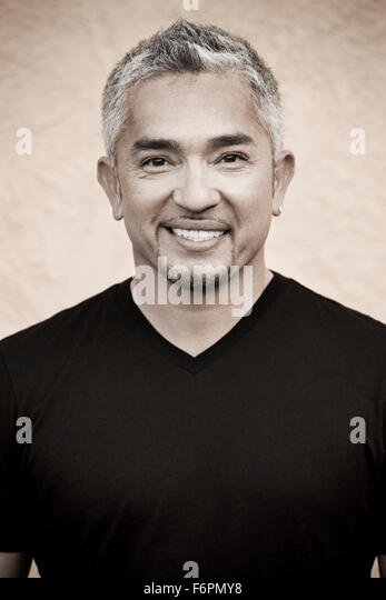 classic forward facing eye contact smiling Ceasr Millan Dog Whisperer famous TV celebrity trainer headshot black - Stock Image