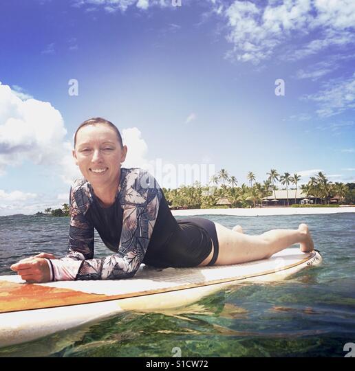 A young woman on a surfboard with Tavarua Island behind her. Tavarua, Nadi, Fiji. - Stock Image