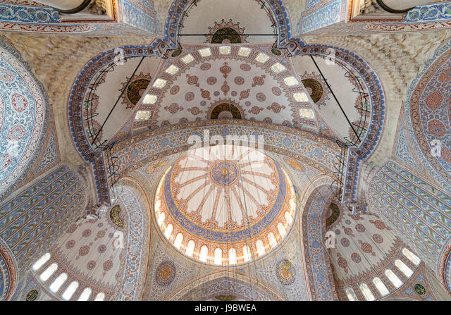 Decorated ceiling of Sultan Ahmet mosque (blue mosque) with huge pillars, domes, arches and stained glass windows, - Stock Image