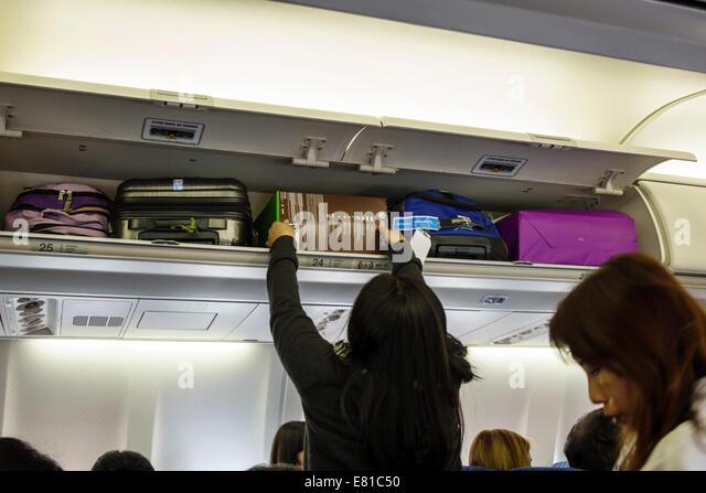 Nevada Las Vegas McCarran International Airport LAS onboard passenger cabin American Airlines flight woman overhead - Stock Image