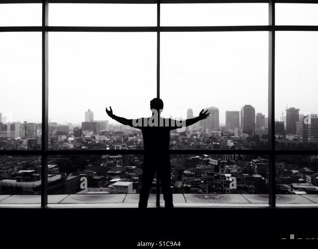 Silhouette of Man Raise his Hands and Seeing Cityscape Landscape View - Black and White - Stock-Bilder