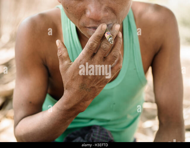 A man takes a smoke break while working in the Bagan Villages - Stock Image