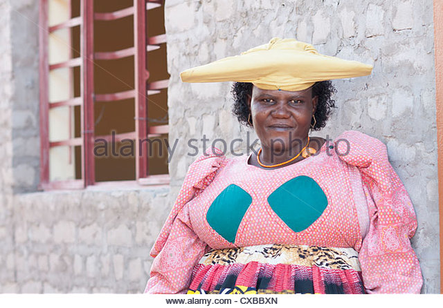 Herero woman in traditional dress and horned hat, Purros village, Kaokoland wilderness region, Namibia, Africa - Stock Image
