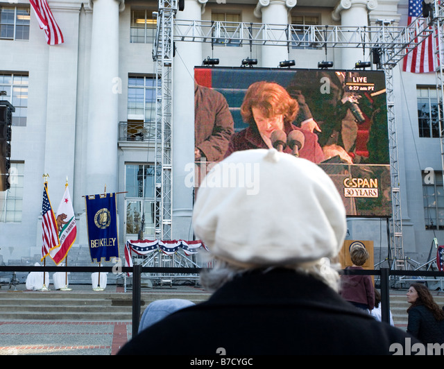 An elderly woman watches Senator Diane Feinstein's welcoming remarks during the 2009 inauguration of Barack - Stock Image