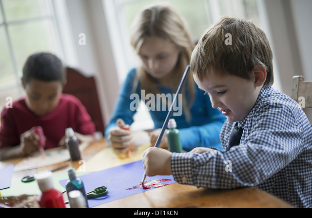 Children in a family home Three children sitting at a table using glue and paint to create decorations - Stock Image