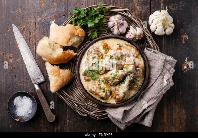 Roasted chicken with creamy garlic sauce in clay pan ketsi on dark wooden background - Stock Image