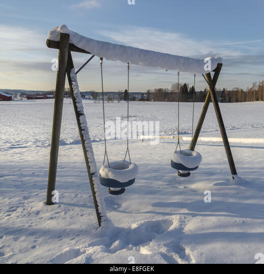 Snow covered swings - Stock Image